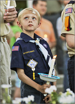 Cub Scout Baileigh Rohde, 8, holds a candle during a candelight vigil in Omaha, Thursday for the four Boy Scouts killed after a twister flattened their Iowa camp Wednesday night.