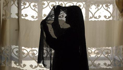 An Afghan prostitute fixes her head scarf to cover her face in her Madame's house in Kabul, Afghanistan. Girls and women in Afghanistan who are accused of prostitution or adultery can be imprisoned or killed.