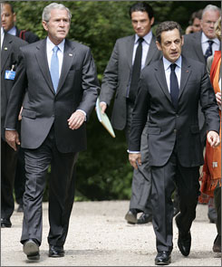 President Bush, left, walks with French President Nicolas Sarkozy after a joint news conference at Elysee Palace.
