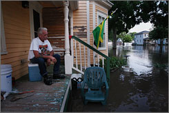 Ron Dickey watches flood water flow in front of his century-old home in Cedar Rapids.