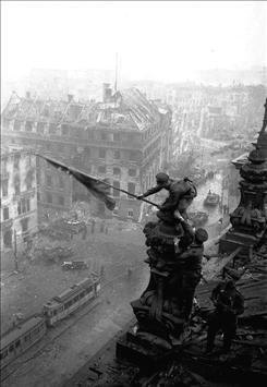 Soviet soldiers hoist the red flag over the Reichstag in Berlin on May 2, 1945. Few know that the iconic image of World War II was staged by the photographer, Yevgeni Khaldei.