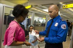 Transportation Security Officer Derrick Ward sports a new policelike uniform and badge as he screens passengers in Baltimore. Screeners will receive the new uniforms throughout the year, as the Transportation Security Administration aims to professionalize its workforce.