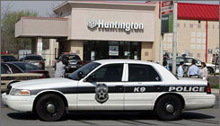 A police car is parked in front of a Hunting bank branch on the east side of Indianapolis where an armed robbery took place in April. A bank teller pregnant with twins was shot in the stomach during the robbery. On average, bank robbers make off with about $10,000 in cash, checks and other property, according to FBI statistics.