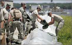 Troops from the 113th Calvary of the Iowa National Guard sandbag the Keokuk, Iowa, wastewater treatment plant, which sits beside the river. Volunteer sandbaggers had worked around the clock to safeguard it from floodwaters.