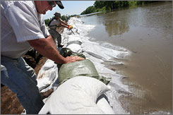 Floodwaters have breached two more levees in western Illinois. Here, members of the Illinois Army National Guard work with farmers and other volunteers to place sandbags on top of levee in Meyer, Ill., on Tuesday.