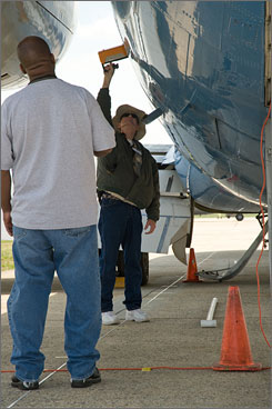 Homeland Security agents scan planes at Andrews Air Force Base, Md., this month during a test of radiation-detection equipment.  Critics say scanning in the USA isn't the answer.
