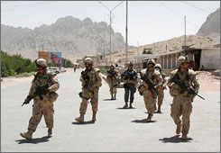 Canadian soldiers with the International Security Assistance Force and an Afghan soldier, center, patrol through Arghandab district, south of Kabul, Afghanistan, on Thurday. Afghan officials say military operations have cleared Taliban militants from the villages they had infiltrated outside of southern Afghanistan's largest city. (