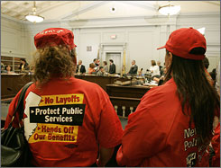 Some wearing shirts urging lawmakers not to reduce state worker benefits, stand in a packed room during a New Jersey Budget Committee hearing  June 19 in Trenton, N.J.