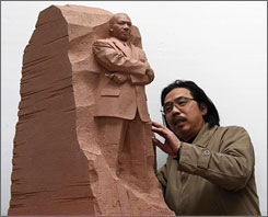 Critics said this earlier version of a statue for the planned Washington memorial to the late Rev. Martin Luther King appeared too confrontational. Here, sculptor Lei Yixin of China looks at his creation, an earlier scale model of the memorial sculpture that has since been ordered altered.