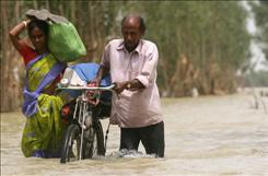 A couple wades through a flooded road at Sabang, about 126 miles west of the eastern Indian city of Kolkata. Flood victims in eastern India took refuge on treetops as monsoon rains swamped homes and continued to spread misery among millions.