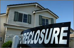 A foreclosure sign is posted in front of a home for sale in Stockton, California.