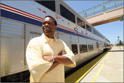 Demetrius Stroud stands near a Northbound Amtrak train at the Emeryville, Calif., train station. Because of high gasoline prices, Stroud is purchasing a home near the Elk Grove, Calif., Amtrak station and will soon commute by train between the Sacramento area and Emeryville rather then drive.