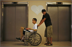 Ami Ortiz, injured when a booby-trapped gift for his family exploded in his home last March, is wheeled in a wheelchair by his brother in Tel Hashomer Hospital in Tel Aviv.