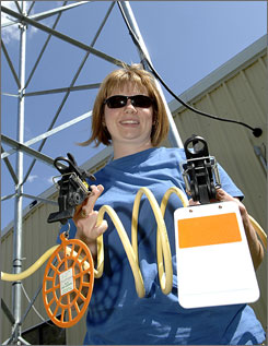 Biologist Misti Schriner holds three types of attachments that are being tested on the overhead power lines along the shore of Lake Audubon in Coleharbor, N.D., in May. The attachments are being used to deter birds from running into the lines.