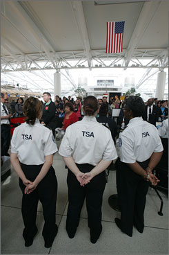 Transportation Security Administration screeners watch passengers at New York JFK airlport. A report says screeners have complained about discrimination, selective hiring, nepotism and management misconduct.