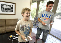 Nolan Kern, 10, left,  plays a video game with au pair Florian Ristau in Tucson, Ariz. Ristau, 25, wants to be an English teacher when he returns to Germany.