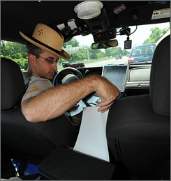 Maryland State Police Cpl. Christopher Corea pulls an e-citation for speeding out of a printer in his patrol car.
