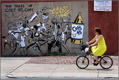 A woman rides her bike past one of the murals advertising malt liquor in Philadelphia that has residents steaming.