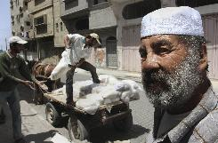 Palestinians load up a donkey cart with bags of donated flour, in Gaza City, Monday, May 5, 2008. Hundreds of thousands of Palestinians living in the Gaza Strip, who live below the poverty line of US$2 a day, have to rely on aid from the United Nations.