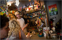 Jon Foster, owner of the Grey Area coffee shop in Amsterdam and a Rhode Island native, helps customers on Wednesday. A ban on smoking tobacco in bars, cafes, restaurants and clubs takes effect July 1 and will affect consumers who like to mix their tobacco with marijuana, which can legally be used in Amsterdam's coffee shops.
