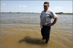 Hoot Jones stands in his flooded corn field on Wednesday in Old Monroe, Mo.