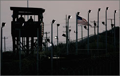 Members of the U.S. military stand watch in a guard tower at dusk along the fence line of Camp Delta.