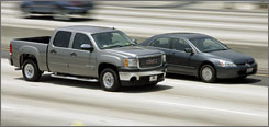 A full-size GMC pickup truck and a more fuel-efficient Honda Accord make their way down the Santa Monica Freeway in Los Angeles Friday. High gasoline prices and the economic downturn are forcing automakers to switch gears far faster than anyone anticipated.
