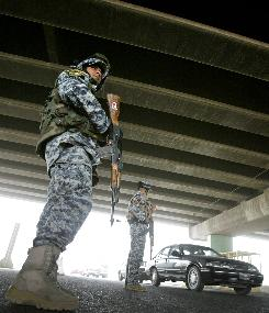 Iraqi policemen stand guard as vehicles drive through a checkpoint, located underneath a highway overpass, in central Baghdad.
