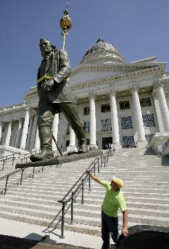 A worker guides a statue of Brigham Young, which had been removed during renovations, in front of the State Capitol building in Salt Lake City on May 30. Workers in the state court system will be exempt from a new state-wide mandatory 4-day work week for most state employees.