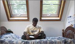 Western Michigan University student Derek Miller studies in his Kalamazoo, Mich., bedroom. His city's tuition program helps pay for his college education.