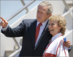 Arriving at the airport Tuesday, President Bush chats with USA Freedom Corps volunteer Cameron Fox in Jackson, Miss.