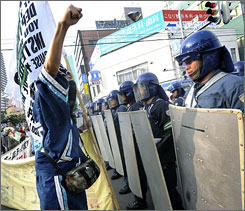 An anti-G8 demonstrator rasies his fist against Japanese riot police in Sapporo ahead of the Hokkaido Toyako G8 Summit 2008.