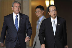 President Bush, left, and Japanese Prime Minister Yasuo Fukuda arrive for a press conference Sunday at the lakeside resort of Toyako, Japan.
