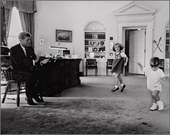 President Kennedy claps as his four-year-old daughter Caroline and son John F. Kennedy Jr., whose second birthday was upcoming Nov. 25, dance in the Oval Office in the White House in October 1962.