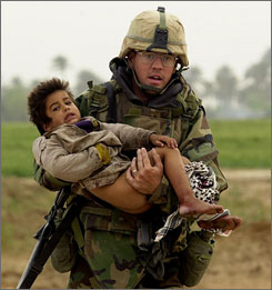 Joseph Dwyer carries Ali, an Iraqi boy, near Al Faysaliyah, Iraq, in 2003.