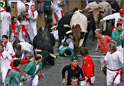 Conde de La Corte ranch fighting bulls chase revelers during the San Fermin festival in Pamplona, Spain on Monday.