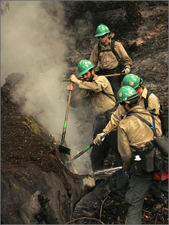 A group of Colorado firefighters work to control a hot spot on a redwood tree during a wildfire in Big Sur, Calif., Monday. Fire crews have managed to defend the village of Big Sur but the fire is only 11% contained and is expected to rage until the end of July.