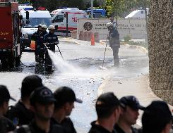Turkish police stand guard in front of the U.S. Consulate as the firemen wash the area after an attack.