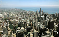 The Chicago skyline with Lake Michigan in the background are visible from atop the Sears Tower Skydeck observation deck in 2006. Chicago is among the cities that saw their populations grow in the last year.