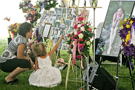 A mother and daughter look at memorials to Brooke Bennett before Bennett's funeral service Wednesday in Randolph, Vt.