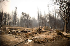 Thousands of people near Sacramento are being evacuated due to wildfires that continue to burn in California. Here, burned trees surround the remains of a home destroyed by fire on Tuesday in rural Butte County.