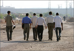 Palestinian Fulbright scholars Zuhair Abu Shaaban, second from right, Osama Daoud, third from right, and Fidaa Abed, fourth from right, walk towards the Erez border crossing between Israel and Gaza to meet U.S. consular officials at the Israeli side of the border on Thursday.