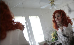 Tempest Storm, an 80-year-old burlesque dancer, fixes her makeup in her Las Vegas apartment.