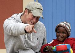 Britain's  Prince Harry, left, jokes with a toddler during his visit at a newly opened center for abused children in Maseru, Lesotho. Harry, 23-year-old lieutenant  is in the impoverished African kingdom  to continue his work with a charity he founded in the memory of his late mother.