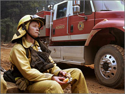 Firefighter Nicole Scott of the Novato Fire District takes a break while working near Jarbo Gap, Calif., on Friday.