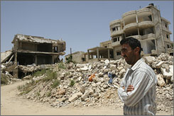 A Lebanese man walks past houses destroyed during the 2006 war between Israel and Hezbollah, in the border village of Aita al-Shaab, Lebanon. In this dusty village on the front lines of Israel's 2006 war with Hezbollah, the Iranian-backed guerrilla group looks as strong as ever. But even at the zenith of its power in Lebanon, Hezbollah's position is fragile.