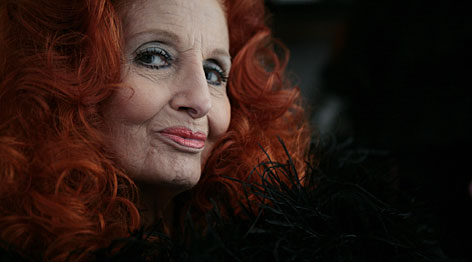 Tempest Storm, an 80-year-old burlesque dancer, tries on her feather boa in her apartment in Las Vegas in June. Her contemporaries, Blaze Starr, Bettie Page and Lili St. Cyr, have died or hung up the pasties.