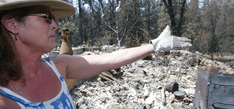"""Virginia Beaudry points to the remains of her home destroyed in a wildfire in Concow, Calif. Beaudry and her 4-year-old Bull Mastiff mix Dog """"Cami"""" plan to live on her property in a trailer as she begins cleanup."""