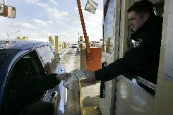 Customs officer Nick Ligerakis hands back a Michigan drivers license and information pamphlet to a driver coming from Canada to Detroit this January. Several border states are working to issue enhanced drivers' licenses that would allow people to enter and leave the U.S. with ease and without other identification.