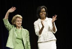 Michelle Obama, right, wife of of Democratic presidential candidate Sen. Barack Obama walks on stage with Washington Gov. Chris Gregoire at a July 17 campaign event in Seattle. Obama headlined the fundraiser for Gregoire's re-election campaign, an event expected to raise about $320,000.